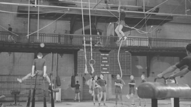 ms shot of young men in gymnasium practicing gymnastics - turnhalle stock-videos und b-roll-filmmaterial