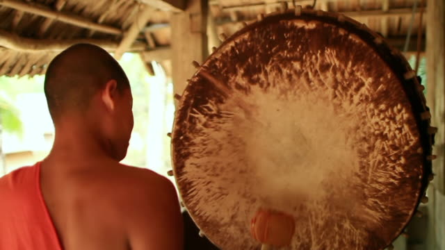 ms tu td slo mo shot of young monk apprentice playing gong and another playing small traditional clash cymbals / mountain village near muang ngoi, luang prabang, laos - cymbal stock videos and b-roll footage