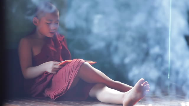 ms shot of young monk sitting on floor reading surrounding by thin veil of smoke from incense sticks / yangon, yangon division, myanmar  - sitting on floor stock videos & royalty-free footage
