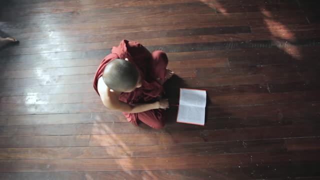MS HA Shot of Young monk sitting on floor reading / Yangon, Yangon Division, Myanmar