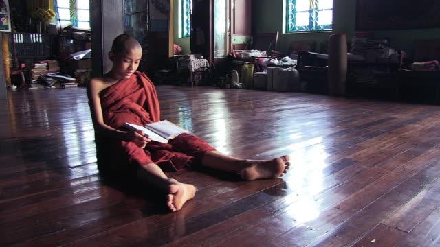 vídeos de stock, filmes e b-roll de ms shot of young monk sitting on floor reading / yangon, yangon division, myanmar  - vestimenta religiosa