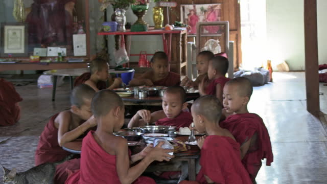 ms shot of young monks sitting and eating together / bagan, mandalay division, myanmar - buddhism stock videos & royalty-free footage