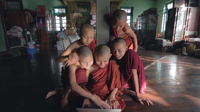 ms shot of young monks sitting around laptop, smiling and laughing / yangon, yangon division, myanmar  - nur jungen stock-videos und b-roll-filmmaterial