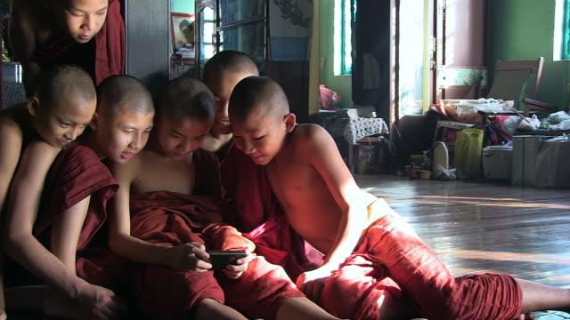 ms shot of young monks sitting on floor around smartphone / yangon, yangon division, myanmar  - ミャンマー点の映像素材/bロール