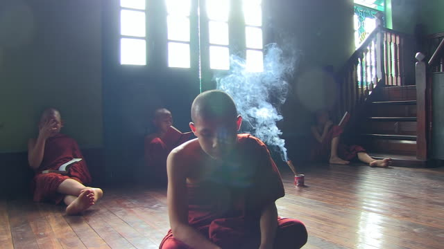 vídeos de stock e filmes b-roll de ms shot of young monks sitting on floor reading surrounding by thin veil of smoke from incense sticks / yangon, yangon division, myanmar  - incenso