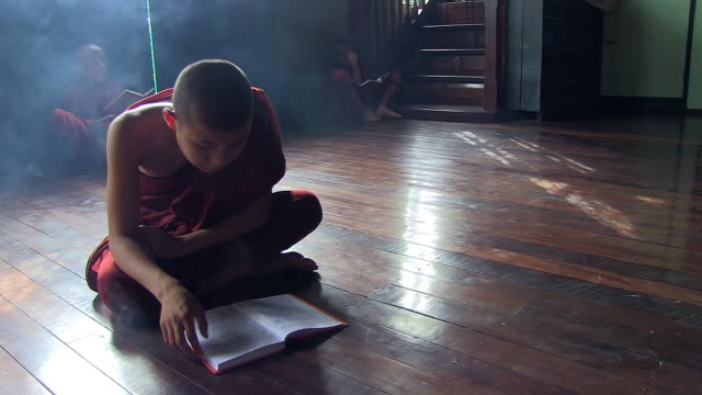 MS Shot of Young monks sitting on floor reading surrounding by thin veil of smoke from incense sticks / Yangon, Yangon Division, Myanmar