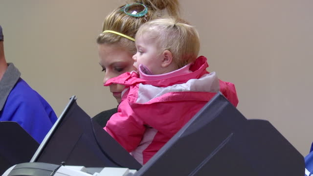 ms shot of young mother holding her daughter in presidential election at union hall / toledo, ohio, united states - elections stock videos and b-roll footage