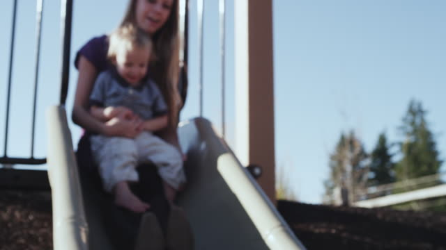 stockvideo's en b-roll-footage met ms r/f slo mo shot of young mother parent going down slide on playground with her toddler baby / beaverton, oregon, united states - speeltuin