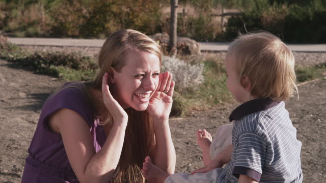 ms shot of young mother parent playing peek boo game with her toddler baby outside on warm summer day / beaverton, oregon, united states - peekaboo game stock videos & royalty-free footage