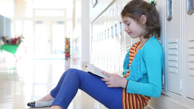 MS Shot of young student reading book in hallway of her school / Santa Fe, New Mexico, United States