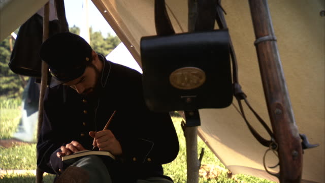 vídeos de stock e filmes b-roll de ms shot of young union soldier sitting inside tent addresses letter and then leaves tent / plum grove, maryland, united states - exército da união