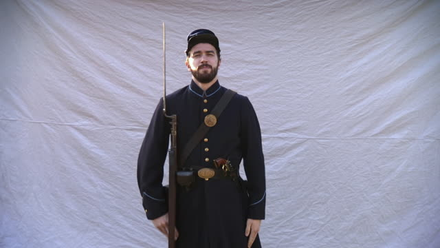 vídeos de stock e filmes b-roll de ws shot of young union soldier wearing full uniform and holding his rifle with bayonet attach walking in front of white background and poses for photograph / plum grove, maryland, united states - exército da união