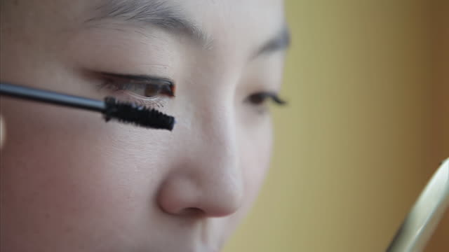 vidéos et rushes de ecu shot of young woman doing makeup in front of mirror / xi'an, shaanxi, china - mascara