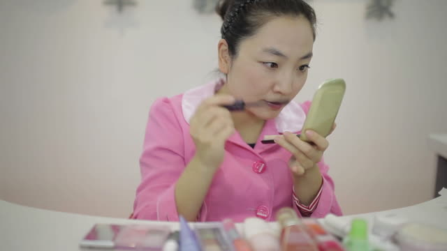 cu pan shot of young woman doing makeup in front of mirror / xi'an, shaanxi, china - メイクアップブラシ点の映像素材/bロール