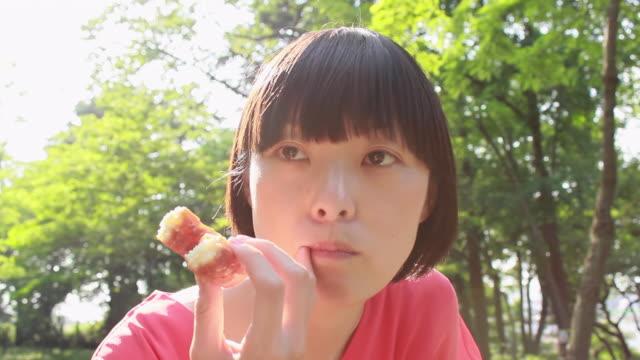 CU Shot of young woman eating doughnuts in park / Nakano, Tokyo, Japan