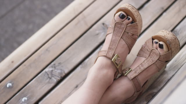 cu slo mo shot of young woman feet are reclining on park bench. she has painted toes and stylish shoes / portland, oregon, united states  - sandal stock videos & royalty-free footage