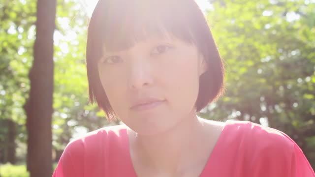 cu shot of young woman in park / nakano, tokyo, japan - 美しい人点の映像素材/bロール