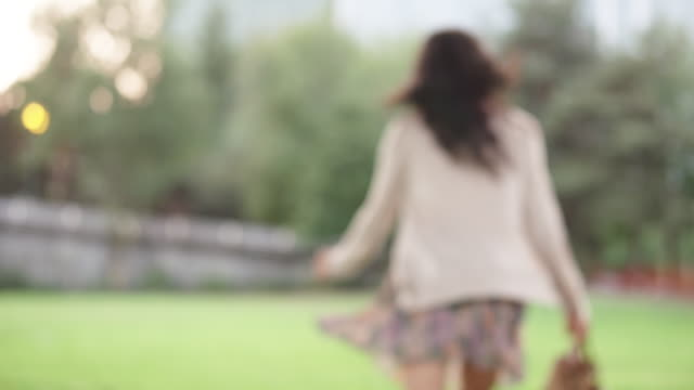 MS SLO MO TU Shot of young woman in skirt and barefoot, turns and runs away on grass / Portland, Oregon, United States
