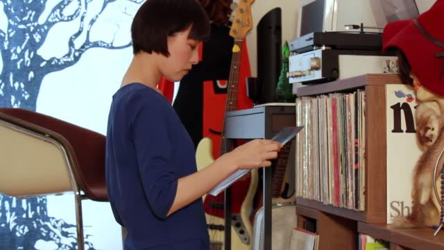 ms shot of young woman select a vinyl record and putting on turntable in her room / nakano, tokyo, japan - 選択点の映像素材/bロール