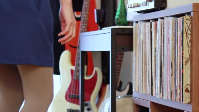 vídeos y material grabado en eventos de stock de ms shot of young woman selecting a vinyl record in her room / nakano, tokyo, japan - choosing