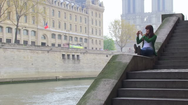 ms shot of young woman sitting and taking picture in city near seine at notre dame / paris, ile de france, france - ile de france stock videos and b-roll footage