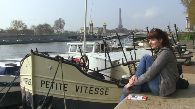 ms shot of young woman sitting by seine river at notre dame / paris, ile de france, france - ile de france stock videos and b-roll footage