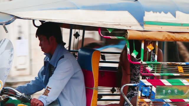MS TS SLO MO Shot of young woman sitting in back of tuk tuk / Luang Prabang, Laos