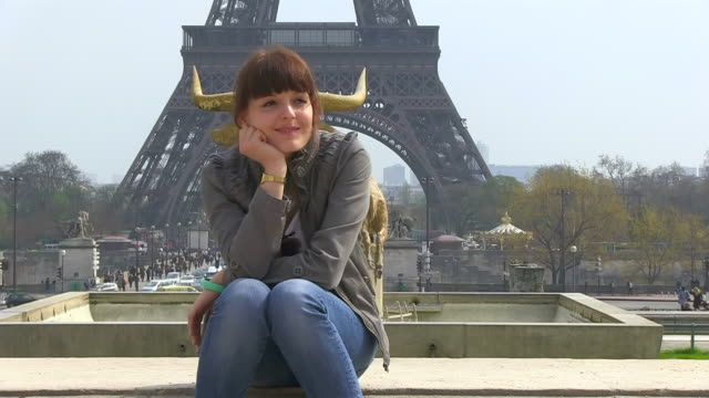 ms shot of young woman sitting in front of eiffel tower / paris, ile de france, france - hand am kinn stock-videos und b-roll-filmmaterial