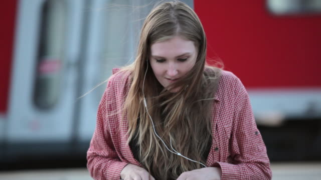 'CU LA Shot of Young woman sitting on platform in train station, listening to music and typing on laptop / Berlin, Germany'