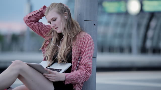 'MS Shot of Young woman sitting on platform in train station, listening to music and typing on laptop / Berlin, Germany'