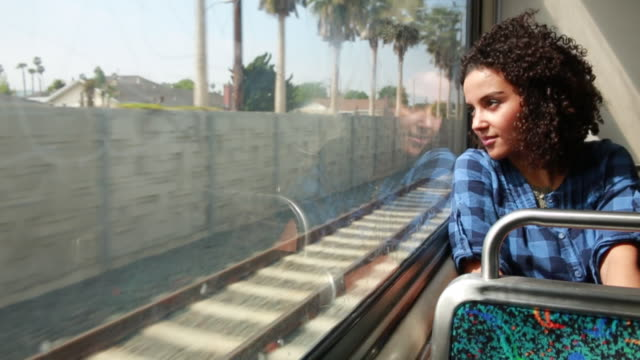MS SLO MO Shot of Young woman smiling and looking out moving metro train window / Los Angeles, California, United States