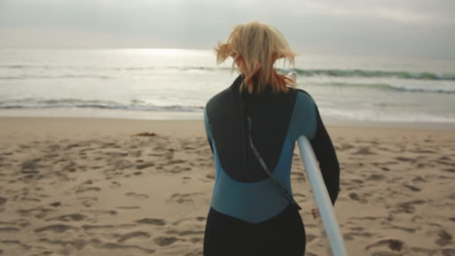 vídeos de stock, filmes e b-roll de ms slo mo ts shot of young woman surfer holding surfboard running towards ocean / venice, california, united states - surfe