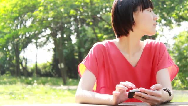 ms shot of young woman using smartphone in park / nakano, tokyo, japan - ピクニック点の映像素材/bロール