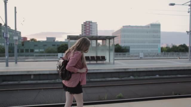 'MS Shot of Young woman waiting and listening to music on platform central station / Berlin, Germany'