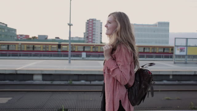 'MS POV Shot of Young woman walking and listening to music on platform central station / Berlin, Germany'