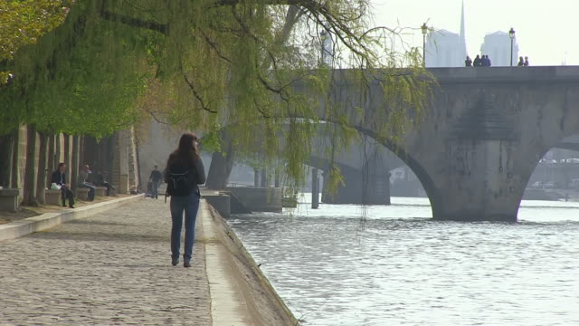 ms shot of young woman walking by seine river at notre dame / paris, ile de france, france - ile de france stock videos and b-roll footage
