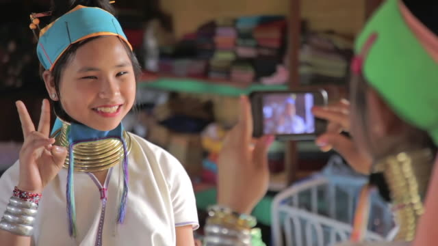 cu shot of young woman wearing neck rings taking picture of another young woman with smartphone / inle lake, shan state, myanmar   - 民族衣装点の映像素材/bロール