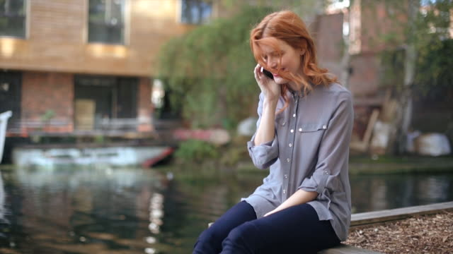 MS Shot of young woman with red hair smiling and talking on mobile phone sitting near waterside development / London, United Kingdom