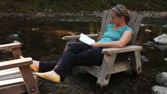 ms shot of young women sitting in adirondack chair and reading book / big sur, california, united states - アディロンダックチェア点の映像素材/bロール