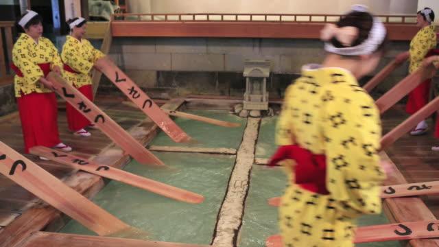 ms shot of yumomi, traditional way for cool down of hot water at most famous hot spring, kusatsu onsen / kusatsu, gunma prefecture, japan  - 温泉点の映像素材/bロール