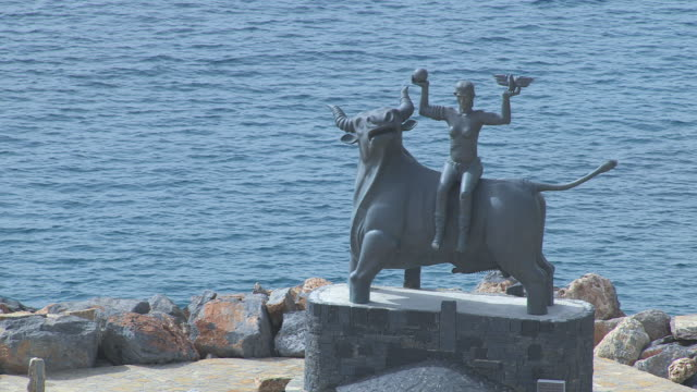 ms aerial shot of zeus statue with europa and bay at distance / agios nikolaos, crete, greece - zeus stock videos and b-roll footage