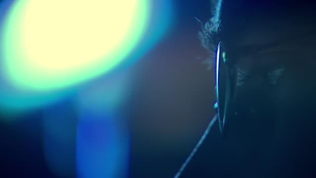 ECU Shot ofbright light highlightsmoving eye of man wearing glasses / United States