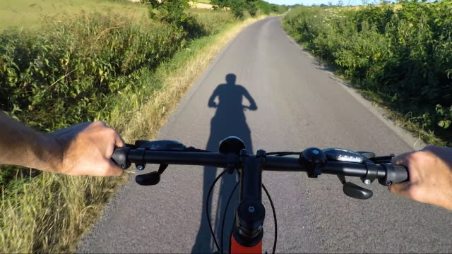 pov shot on bicycle ride along country road - wearable camera stock videos & royalty-free footage