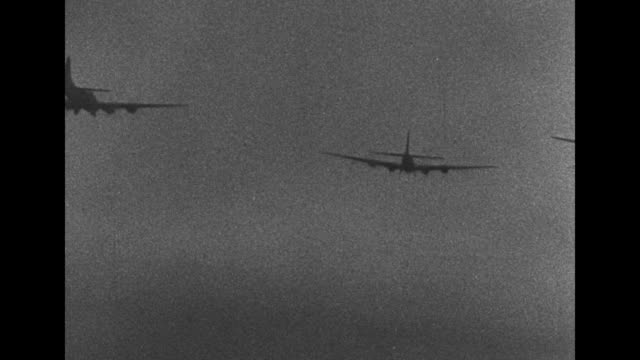 shot on bomber through side window with machine gun in it / two shots from bomber of bomber flying above it / three shots from bomber of three... - 爆撃機点の映像素材/bロール