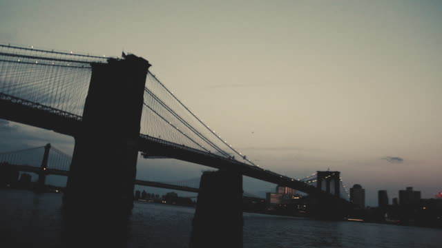 shot on film - new yorkcity's brooklyn bridge at dusk - 4k - east river stock videos & royalty-free footage