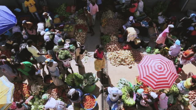 WS HA SLO MO Shot over African market street vendors selling fresh vegetables and fruits / Santiago, Cape Verde