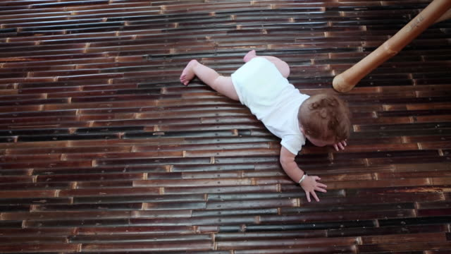 ms ha shot over baby trying to crawl moving ahead / ubud, bali, indonesia - krabbeln stock-videos und b-roll-filmmaterial