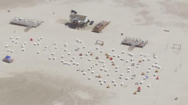 ws aerial zi shot over beach chairs at coastline / sankt pete ording, schleswig holstein - deutsche nordseeregion stock-videos und b-roll-filmmaterial