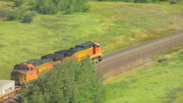 ms aerial ts shot over bnsf locomotive traveling on train track in glacier national park / montana, united states - glacier national park us stock videos and b-roll footage