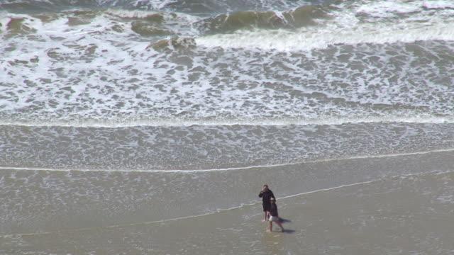 WS AERIAL Shot over couple walking along coastline / Sankt Pete Ording, Schleswig Holstein